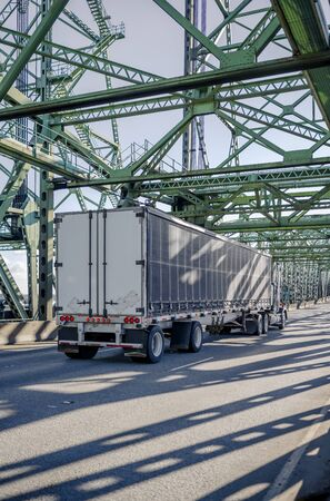 Dark big rig classic semi truck with chrome accessories transporting commercial cargo in covered black dry van semi trailer driving on the truss Interstate drawbridge across the Columbia River Stock Photo