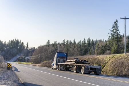 Industrial transportation Big rig blue classic semi truck with powerful diesel engine transporting heavy metal profile on flat bed semi trailer driving on the road with trees and hill on the side