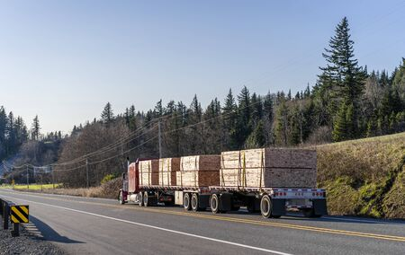 Industrial grade transportation red classic big rig long haul diesel semi truck transporting stacked piles of lumber cargo on two flat bed semi trailers running on the road with hill and trees