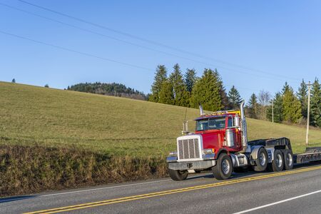 Industrial transportation Red day cab big rig diesel semi truck with empty step down semi trailer for carry oversized loads running on the road with field hill on the side to loading warehouse place