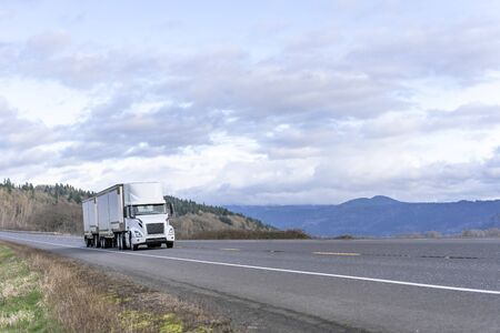 Industrial grade transportation road train white big rig long haul diesel semi truck transporting commercial cargo in two dry van semi trailers running on the road with sky view at sunny day Standard-Bild