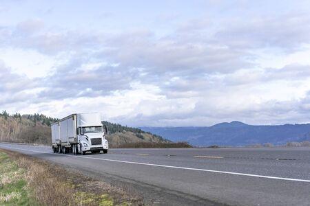 Transport de qualité industrielle train routier blanc gros camion semi-remorque diesel longue distance transportant des marchandises commerciales dans deux semi-remorques fourgons secs fonctionnant sur la route avec vue sur le ciel aux beaux jours Banque d'images
