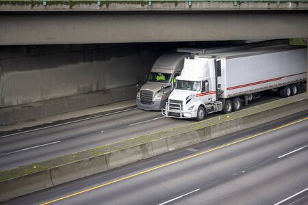 Two different industrial grade big rig semi trucks with diesel engines and refrigerator semi trailers transporting commercial cargo running on the divided highway under the concrete bridge  写真素材