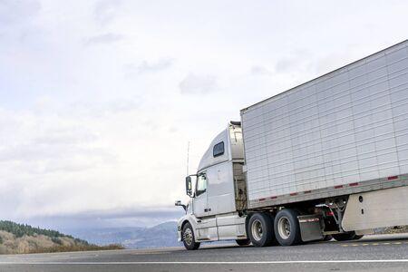 Potężna, długodystansowa, duża platforma przemysłowa naczepa z silnikiem wysokoprężnym, transportująca komercyjny ładunek żywności w naczepie chłodniczej, poruszającej się po płaskiej drodze z widokiem na niebo i wzgórza w wąwozie Columbia Zdjęcie Seryjne