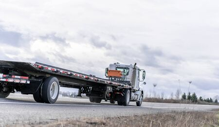 Industrial transportation Big rig day cab semi truck with powerful diesel engine transporting empty lifting flat bed semi trailer driving on the road with a trees and clouds on the side