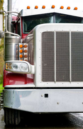 Big rig bonnet diesel industrial wet red semi truck chrome accessories standing on the street road parking in raining weather waiting for cargo load for next delivery 写真素材