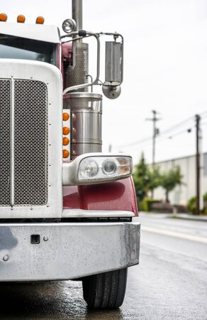 Big rig bonnet diesel industrial wet red semi truck chrome accessories standing on the street road parking in raining weather waiting for cargo load for next delivery 版權商用圖片