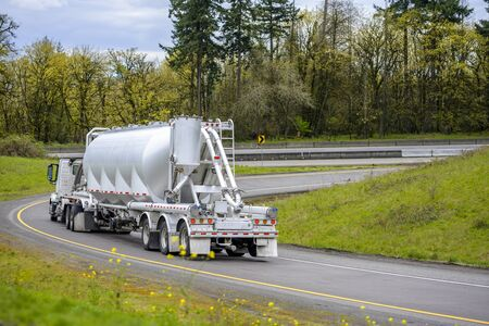 Big rig classic American industrial bonnet diesel semi truck transporting commercial cargo in closed bulk semi trailer running downhill turning on the highway entrance with green trees on the sides
