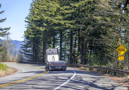 Industrial dark blue big rig classic long haul semi truck with vertical chrome exhaust pipe transporting empty flat bed semi trailer moving on the winding forest road in Columbia Gorge