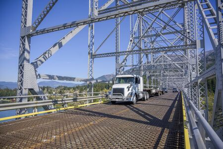 White day cab powerful big rig diesel semi truck for local freights with empty step down semi trailer driving on the silver truss bridge across Columbia River to warehouse for the load