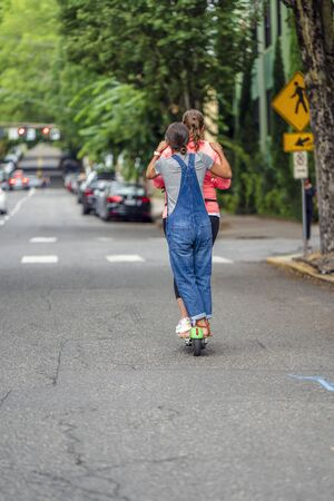 Two young girls ride an electric scooter together on the street of a modern city, taking the opportunity to save money on renting one scooter risking falling and getting injured are experiencing fate