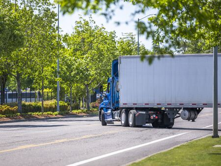 Blue day cab industrial diesel big rig semi truck with roof spoiler for reduce air resistance and improve aerodynamics transporting cargo in dry van semi trailer turning on the green city street road