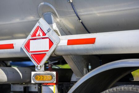 Powerful industrial grade diesel big rig semi truck transporting fuel cargo in tank semi trailer with a sign to indicate the transport of hazardous flammable liquids on the side of the tank