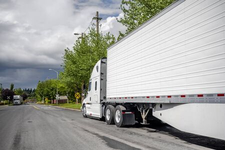 Big rig long haul industrial freight white semi truck with grille guard and refrigerator semi trailer with skirt waiting for commercial cargo parked on the street road near the warehouse buildings Foto de archivo