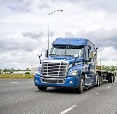 Industrial professional long haul big rig blue diesel semi trucks with low cab transporting commercial cargo on flat bed semi trailers running on the straight wide multiline highway road