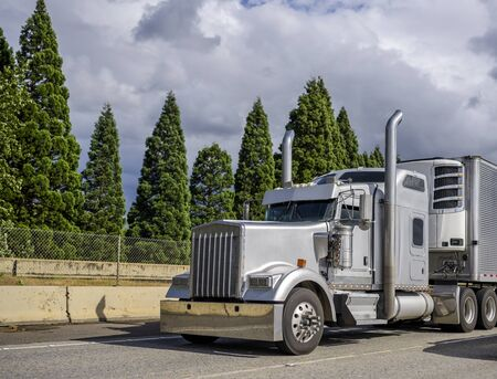 Gray classic bonnet big rig stylish semi truck with chrome accessories transporting commercial cargo in corrugated aluminum refrigerator semi trailer running on the multiline road at sunny day