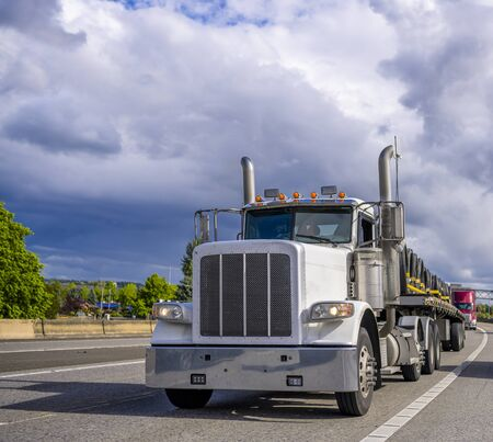 Powerful loaded classic big rig white day cab semi truck with vertical exhaust pipes transporting wire rolls on the flat bed semi trailer running on the multiline wide highway road