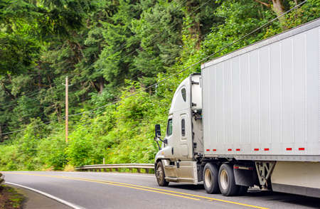 White bonnet big rig long hauler industrial semi truck transporting freight commercial cargo in dry van semi trailer running on the winding road in forest at Columbia Gorge National Recreation Area Banque d'images