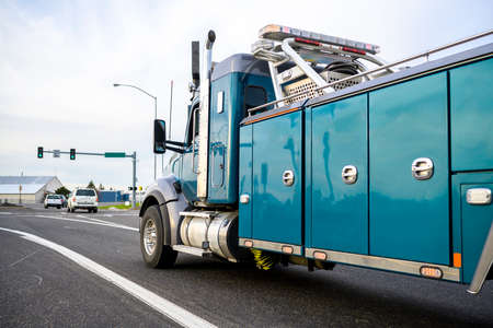 Powerful heavy-duty big rig mobile tow semi truck with emergency lights and towing equipment running on the city street with traffic light going to help broken semi trucks go to a repair shop Imagens