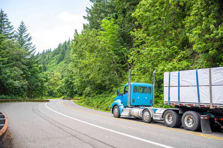 Big rig blue day cab semi truck with vertical exhaust pipes transporting covered stacked lumber wood on flat bed semi trailer running on the winding forest road in Columbia Gorge National Scenic Area Imagens