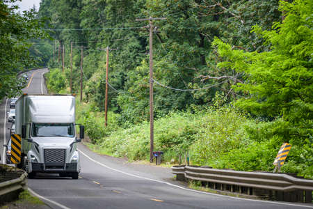 White bonnet big rig long hauler industrial semi truck transporting freight commercial cargo in dry van semi trailer running on the winding road in forest at Columbia Gorge National Recreation Area Imagens