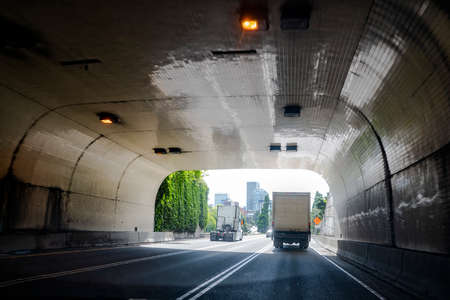 Big rig white shiny industrial diesel high cab powerful semi truck tractor without of semi trailer running on wide multiline road through the tunnel beside with another semi truck with box trailer 스톡 콘텐츠