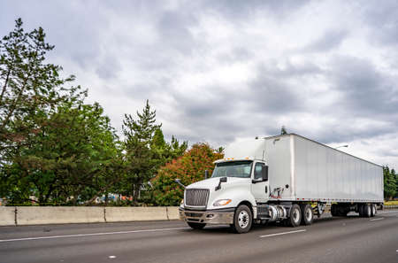 Big rig white industrial diesel day cab semi truck with roof spoiler and dry van semi trailer transporting commercial cargo load driving on the wide multiline highway road with trees on the side