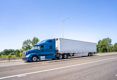 Big rig blue bonnet semi truck with high cab and long refrigerator semi trailer transporting commercial cargo load driving on the wide highway road with bridge and concrete safety fence on the side