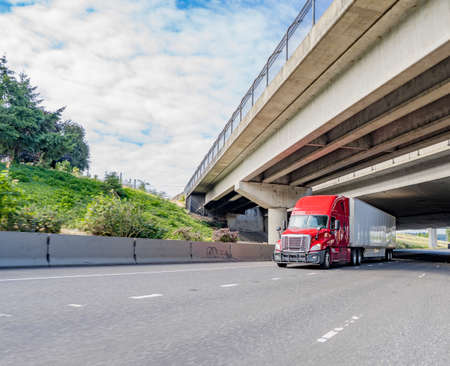 Big rig red bonnet industrial diesel semi truck with high cab and long dry van semi trailer transporting commercial cargo load driving on the wide highway road under concrete bridge intersection