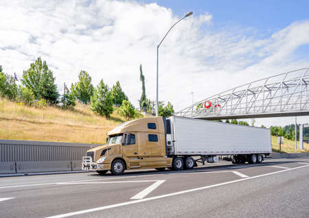 Big rig yellow bonnet semi truck with grille guard and long refrigerator semi trailer transporting commercial cargo load driving on the wide highway road with bridge and concrete wall on the sidehill Archivio Fotografico