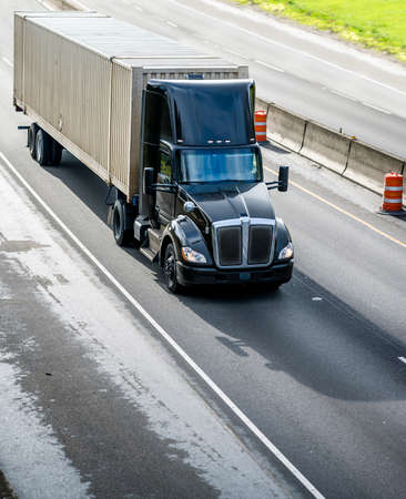 Stylish Heavy loaded classic black big rig semi truck with roof spoiler transporting commercial cargo at container on semi trailer running on the straight wide divided multiline highway road