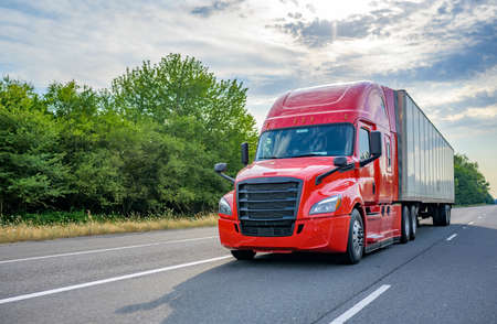 Heavy loaded classic red big rig semi truck with high roof transporting commercial cargo at dry van semi trailer running on the straight wide divided multiline highway road for timely delivery