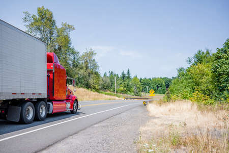 Loaded industrial red big rig semi truck with grille guard transporting frozen commercial cargo in long refrigerator semi trailer running on the winding road in Columbia Gorge National Area