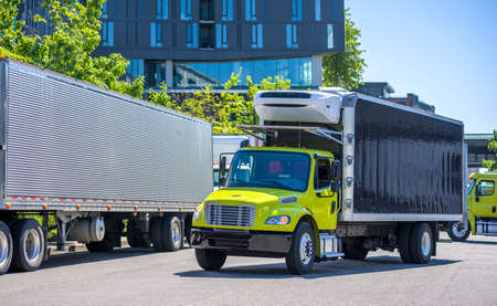 Medium duty professional freight powerful rigs industrial diesel semi trucks with refrigerated box trailers running to warehouse dock for loading cargo for the next delivery Reklamní fotografie