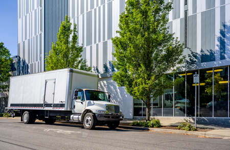Industrial Medium-sized professional Big rig day cab semi truck with box trailer unloading delivered cargo standing on the urban city street with multilevel residential apartment buildings