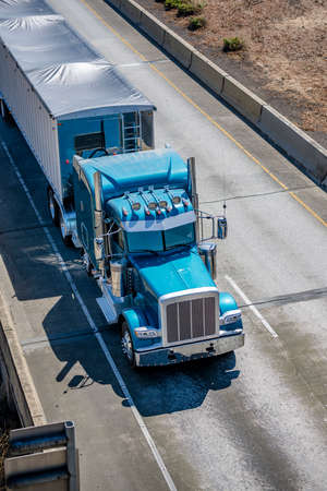 Bright blue industrial diesel long haul classic big rig semi truck tractor transporting commercial cargo in covered semi trailer with frame driving on the overpass intersection of interstate highway