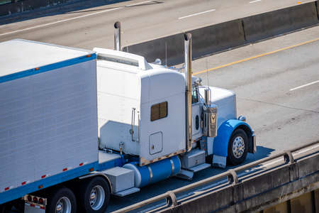 Powerful white classic big rig diesel semi truck transporting frozen commercial cargo on refrigerator semi trailer running on the divided multiline highway road intersection