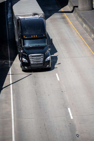Powerful bright black classic big rig diesel semi truck transporting covered commercial cargo on refrigerator semi trailer running on the divided multiline highway road intersection