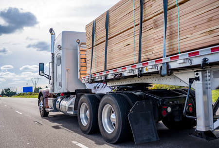 White classic powerful bonnet American big rig professional semi truck tractor transporting tightened wood lumber cargo on flat bed semi trailer running on wide multiline highway road