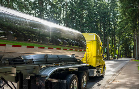 Shiny yellow industrial big rig diesel semi truck tractor with extended cab compartment transporting fuel in stainless steel tank semi trailer running on the road with green trees forest