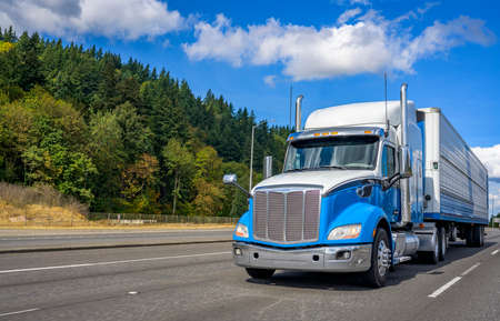 Blue and white big rig industrial grade bonnet long hauler diesel semi truck with refrigerator semi trailer running with commercial cargo on the wide highway road with green hill on the side Stock fotó