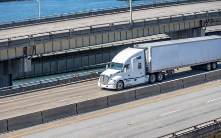 White bonnet industrial grade diesel big rig semi truck tractor transporting commercial cargo in refrigerated semi trailer running on the multilevel overpass road intersection along the river