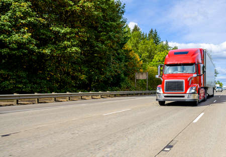 Red big rig industrial grade bonnet long hauler diesel semi truck with high roof cab and refrigerator semi trailer running with commercial cargo on the wide highway road with green trees hillside Stock fotó