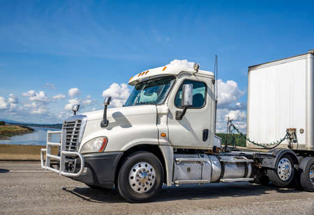 Powerful big rig white industrial grade day cab diesel semi truck with pipe grille guard transporting commercial cargo in dry van semi trailer running on the wide highway road at sunny day Stock fotó