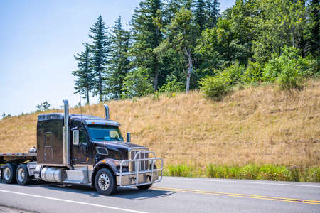 Dark professional industrial grade diesel big rig semi truck tractor with long empty flat bed semi trailer driving to warehouse on the summer winding road with dry grass and green trees on the hills