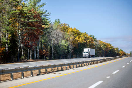 Industrial white day cab powerful big rig semi truck tractor transporting cargo in container trailer running on the divided highway with autumn maples trees line in New Hampshire New England