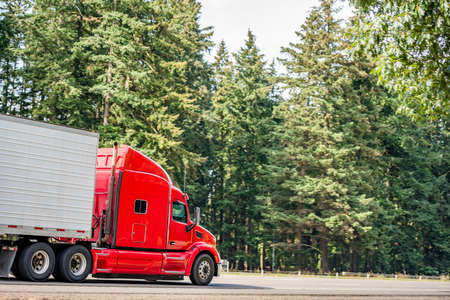 Bright red long hauler big rig red industrial semi truck transporting frozen and chilled foods in refrigerator semi trailer running on the straight highway road with green trees on the side