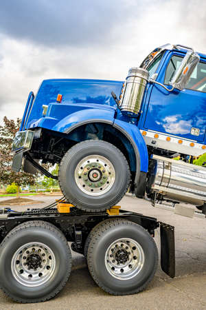 Powerful day cab industrial big rig semi truck towing another semi trucks tractors on the chassis frame each subsequent forming a kind of semi truck train took a break and standing on parking lot