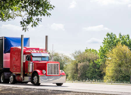 Big rig red classic American industrial semi truck tractor with sleeper cab compartment for truck driver rest transporting cargo in dry van semi trailer driving on the highway road with trees Stock fotó