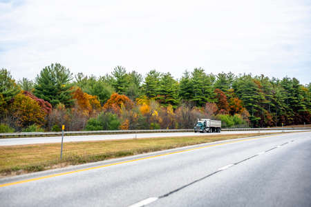 Big rig day cab for local work sides green semi tip truck with covered dump trailer running with cargo on the divided highway road with autumn maple trees in Vermont New England Stock fotó